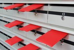 Briefkästen und rote Umschläge Stockbild