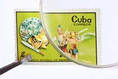 Briefmarke unter Vergrößerungsglas mit Pinzette stockfotografie