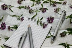 Briefpapier auf kleinen purpurroten Blumen und silbernem Band Stockbilder