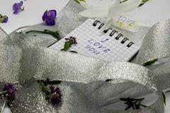 Briefpapier auf kleinen purpurroten Blumen und silbernem Band Stockfoto