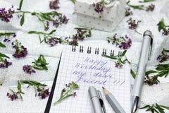 Briefpapier auf kleinen purpurroten Blumen und silbernem Band Lizenzfreie Stockfotos