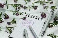 Briefpapier auf kleinen purpurroten Blumen und silbernem Band Stockfotografie