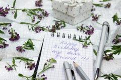 Briefpapier auf kleinen purpurroten Blumen und silbernem Band Lizenzfreie Stockfotografie