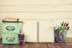 Briefpapier, bunte Bleistifte und offenes Notizbuch auf dem Tisch Stockfotografie