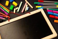 Briefpapier und hölzernes Brett für Schule auf einem schwarzen Hintergrund stockbild