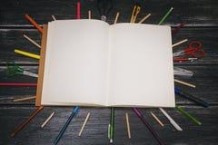 Briefpapier und Notizbuch - bunte Bleistifte und Materialausrüstung auf hölzernem Hintergrund Lizenzfreie Stockbilder
