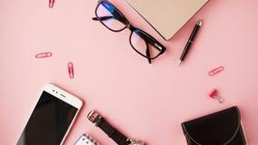 Briefpapier, weißer Smartphone, Gläser, Stift, Geldbörse, Uhr, Kalender, Notizbuch Rosa Hintergrund stockfoto