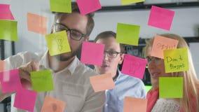 Briefpapieranzeigen-Zeitplanbrett Treffende Geschäftsleute und Gebrauchspost-itanmerkungen, um Idee zu teilen Diskussion - Geschä stock footage