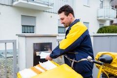 Briefträger, der Buchstaben an Briefkasten der Empfängers liefert Lizenzfreie Stockfotos