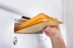 Briefträger, der Buchstaben in Briefkasten einsetzt Stockbild