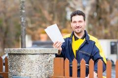 Briefträger, der Buchstaben an Briefkasten der Empfängers liefert stockbild