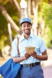 Briefträger Walking Along Street, das Buchstaben liefert Stockfotografie