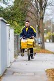 Briefträger, der sein Frachtfahrrad durchführt Post reitet Stockfotografie