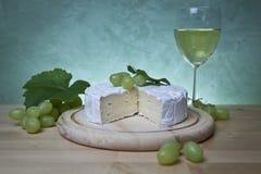 Briekäse, Wein und Trauben Stockbilder