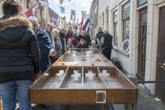 Niños que juegan el shuffleboard holandés en la calle durante festiva Imagenes de archivo