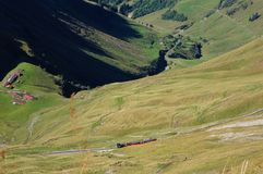 Brienzer Rothorn bahn amoung green field and the mountain on the way up to Brienzer Rothorn Stock Image