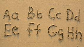 Brieven van het alfabet op zandig strand wordt geschreven dat Royalty-vrije Stock Afbeeldingen