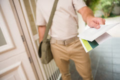 Brievenbesteller die een brief levert stock foto's