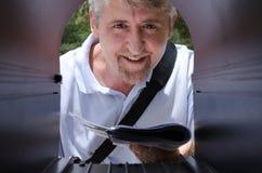 Brievenbesteller die een levering van brieven maakt aan een brievenbus stock foto
