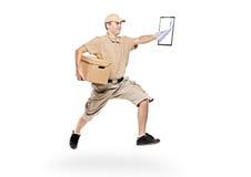 Brievenbesteller in een haast die pakket levert Royalty-vrije Stock Foto