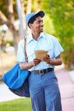 Brievenbesteller Walking Along Street die Brieven leveren stock foto