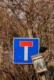 Brievenbus en verkeersteken vast op een concrete pijler stock afbeelding