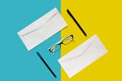Brievenenvelop, oogglazen en pennen stock foto