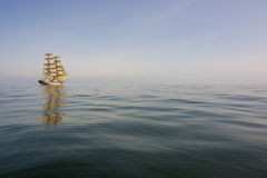 Brig drifting at dead calm sea Stock Photography