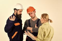 Woman amend plan of repair. Supervisor not satisfied with renovation. Brigade of workers, builders in helmets, repairers. Brigade of workers, builders in helmets Royalty Free Stock Photos