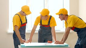 Brigade of workers in uniform looking at project of building. Planning repair concept. People, building and renovation concept stock photography