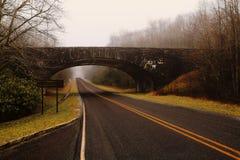Brige au-dessus de route par une forêt avec le brouillard Images stock