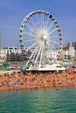 BRIGGHTON - JULHO 14,2013 - veem a areia dourada de Brigghton beira-mar à roda e ao parque de diversões de ferris com os grupos d Foto de Stock