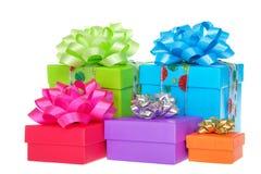 Brighly färbte Geschenke mit den Bögen, die auf Weiß lokalisiert wurden Stockfotografie