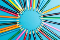 Bright abstract background of multi-colored pencils in the shape of a circle, top view. Space for text royalty free stock photos