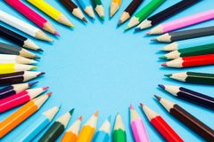 Bright abstract background of multi-colored pencils in the shape of a circle, top view. Space for text stock images