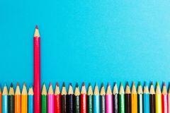 Bright abstract background of multicolored pencils on a blue background, top view. Space for text royalty free stock photo