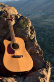 Bright Acoustic Guitar in the Mountains. A bright colored acoustic guitar against rocks on a mountain cliff Stock Photo