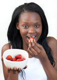 Bright african woman eating strawberries Stock Photos