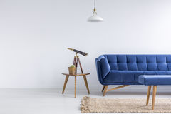 Bright apartment with blue sofa. Bench, rug, lamp and table Stock Photo