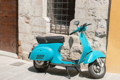 Bright aqua motor scooter parked in Italian village street. Stock Image