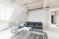 Bright attic living room with wooden ceiling beams. royalty free stock photography
