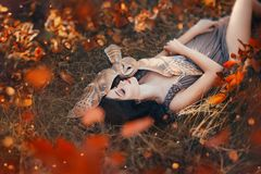 Bright autumn art photo, goddess rests in autumn orange forest under protection of cute little owl, girl with dark hair royalty free stock photos