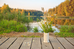 Bright autumn field bouquet of flowers in the hand-made ceramic vase at a bridge on the pond/lake. Autumn wood on the background. Bright autumn field bouquet of Stock Photo