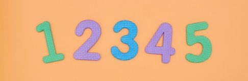 Bright, baby rooms from 1 to 5 are made of colored baby foam isolated on peach background. color numbers close-up royalty free stock photo