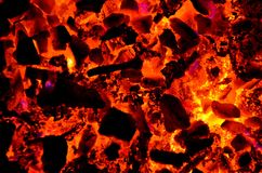 Bright background consisting of burning coal, wood and non-ferrous metal. Burning chips of non-ferrous metals on coal with wood as a background Stock Images