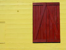 Bright Background Wall. Bright yellow barn wall with red door Stock Photo