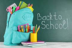 Free Bright Backpack With School Stationery On Wooden Table Near Green Chalkboard Stock Photos - 151645743