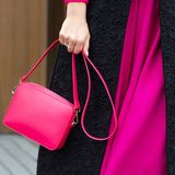 A bright bag in women`s hands. Leather bag. Stock Photos