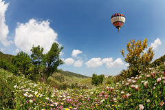 A  bright balloon flying over hills Stock Photos