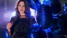 Bright balloons into hands of happy brunette in backlight in fog at evening event. Bright balloons into hands of happy brunette with beautiful hair in backlight stock footage